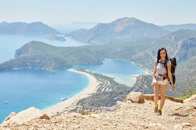 Женщина, пешая прогулка по ликийскому пути с рюкзаком. фетхие, олюдениз. прекрасный вид на море и пляж. поход в горы турции