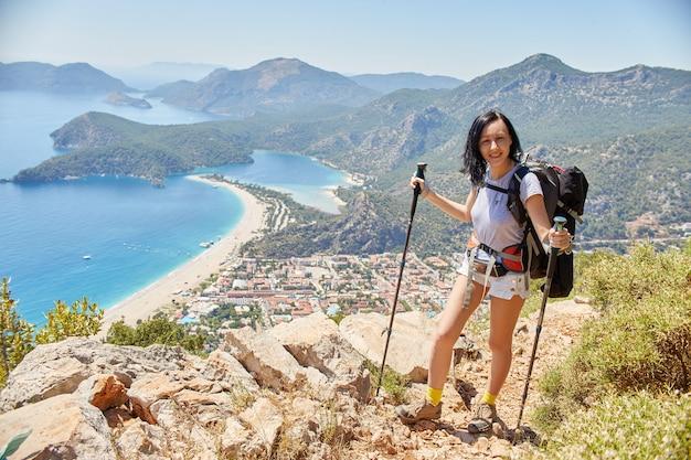 バックパックでリシアンの方法をハイキングする女性。フェティエ、オルデニズ。海とビーチの美しい景色。トルコの山でのハイキング