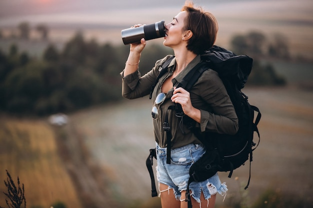 Woman hiking in the mountains and drinking water
