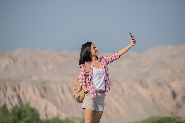 Donna che fa un'escursione in montagna in piedi sulla cresta rocciosa sommitale con zaino e palo che si affaccia sul paesaggio, felice femmina che fa autoritratto in montagna