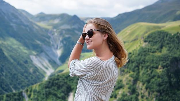 Woman hiking in mountains at sunny day time. view of kazbegi, georgia