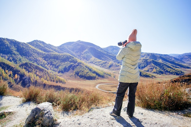 Woman hiking in mountains with camera.  woman with a photo camera enjoys the beauty of nature hiking in the mountain peak.