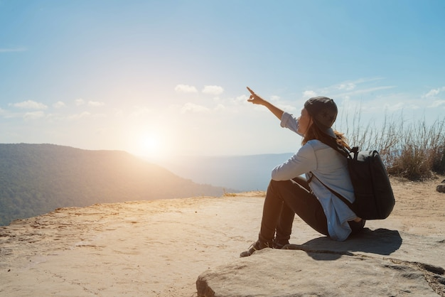 空を指してハイキングする女性は、太陽の光のために山の美しい景色をお楽しみください
