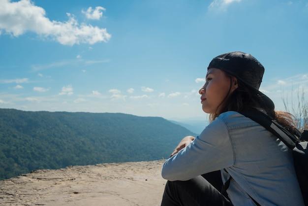 座ってハイキングする女性は、太陽の光のために山の美しい景色をお楽しみください