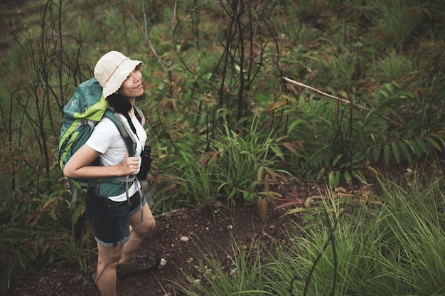 Woman hiking at sunset mountains with heavy backpack travel lifestyle wanderlust adventure concept summer vacations outdoor alone into the wild