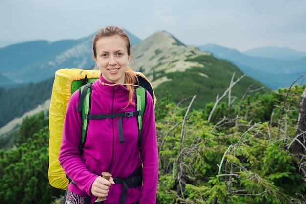 トレッキングスティックとバックパックでハイキングの女性