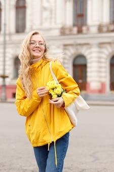 街で花と黄色のジャケットの女性ヒップスターは散歩に落ちる
