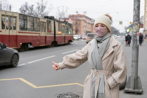 마스크를 착용하는 동안 도시에서 히 치 하이킹하는 여자