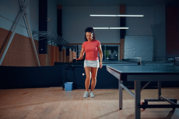 Woman hits a ball, table tennis training in gym