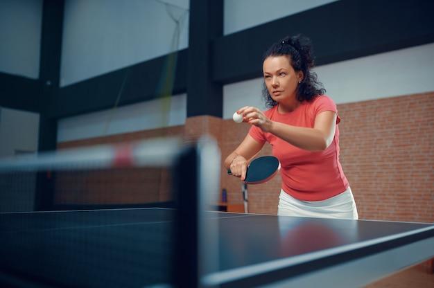 Woman hits ball at the wall