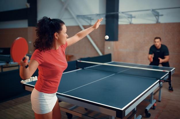 Женщина бьет мяч, играя в настольный теннис