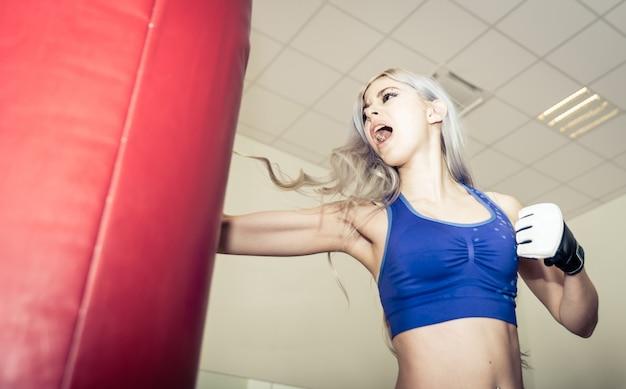 Женщина ударяет тяжелую сумку в бокс в спортзале