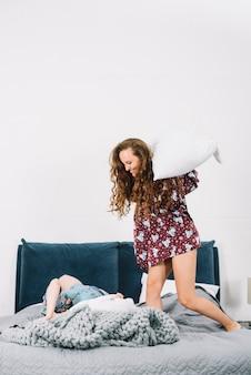 Donna che colpisce la sua amica con il cuscino sul letto