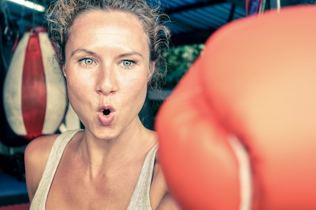 Woman hitting with punch on gritty determination - boxing sport concept