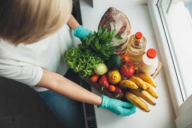 격리 기간 동안 장갑을 끼고있는 동안 과일과 야채를 쌓아 두는 여성