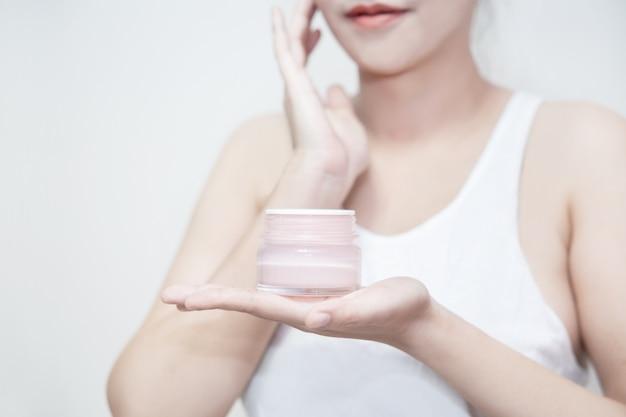 女性は彼女の手で保湿クリームを保持し、彼女の顔にクリームを適用します