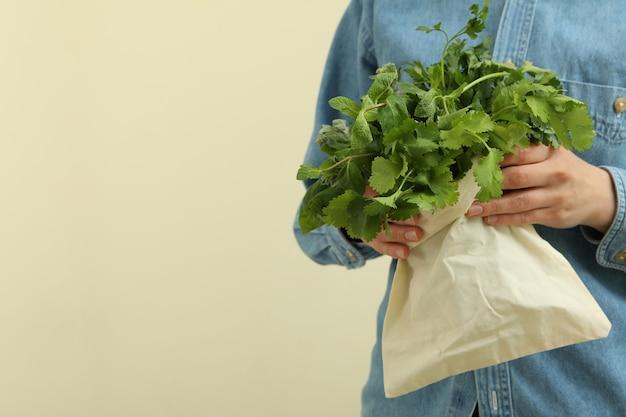 女性はベージュのハーブとバッグを保持します