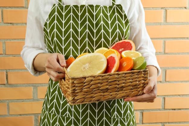 女性はレンガの壁の背景に柑橘類のバスケットを保持します。