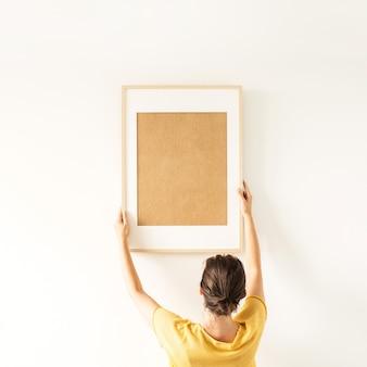 女性は白い表面に空のコピースペースで空白のフォトフレームを保持します