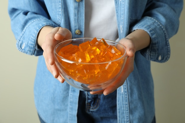 女性はおいしいオレンジゼリーのボウルを保持します