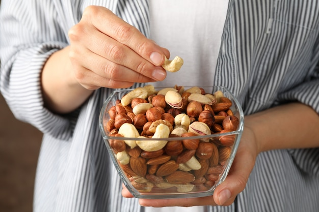 Woman hold bowl with different nuts.
