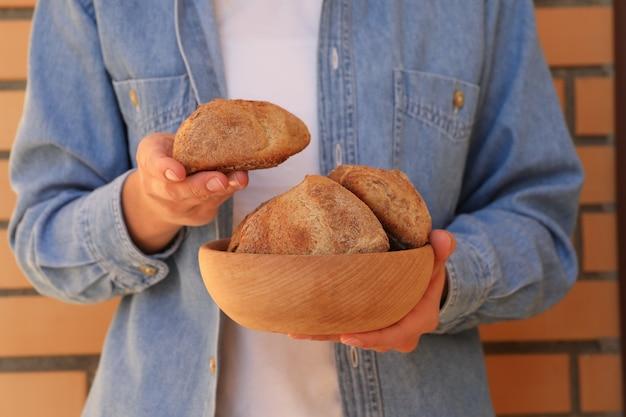 女性は焼きたてのパンとボウルを保持します