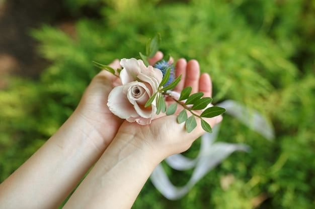 Woman hold bracelet for bridesmaid made from fresh pink rose
