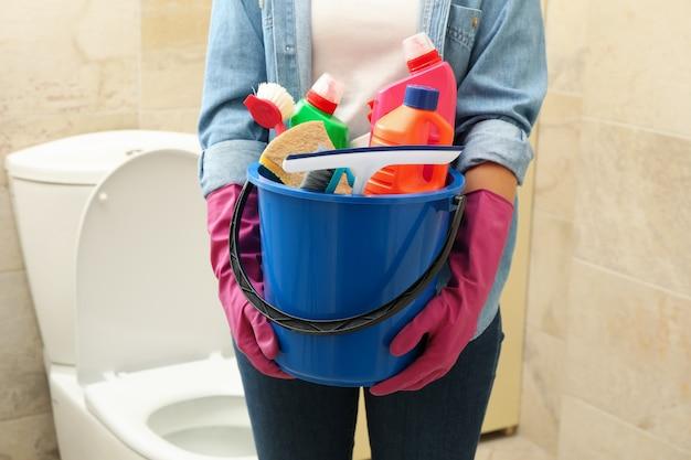 女性はモダンなバスルームでクリーニング製品とバケツを保持します