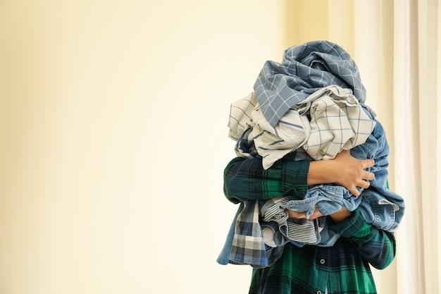 女性はしわくちゃの洗濯物の束を保持します