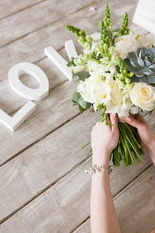 女性は明るい灰色の背景に白いバラとジューシーな束を保持します。ブーケの下での愛という言葉。装飾、ソーシャルメディアの写真、ギフト、結婚式、人間関係の概念。