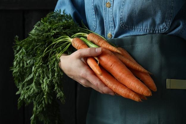 Женщина держит морковь на темном деревянном фоне