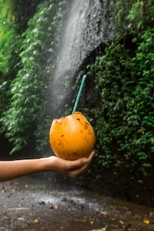 Woman hold coconut drink in hand next to waterfall.