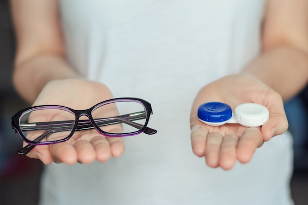 Woman hold contact lenses and glasses in hands. concept of choice of vision protection