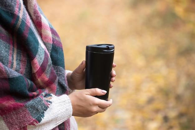Женщина держит чашку в лесу, осенняя фотография