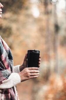 女性が森の中でカップを保持、秋の写真