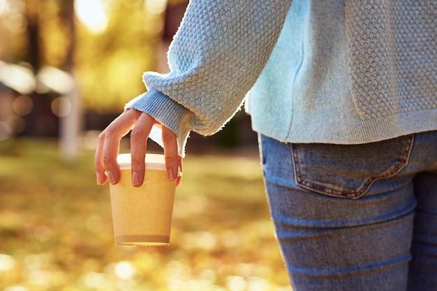 女性は秋の公園でコーヒーテイクアウトのカップを保持します。