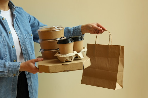 Женщина держит контейнеры для доставки еды на вынос на бежевой поверхности