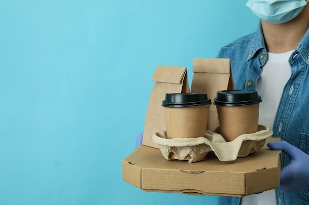 Женщина держит контейнеры для доставки еды на вынос на синей поверхности