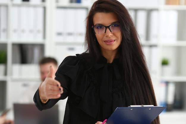 Женщина держит блокнот для документов, подает руку в знак приветствия