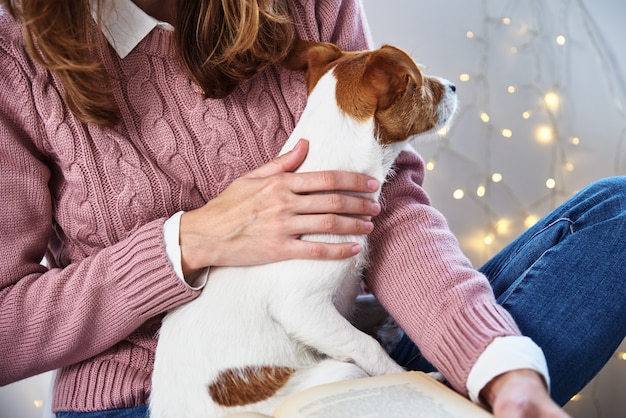 Woman hold dog and reading book. relaxing together with pet