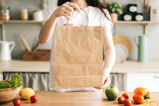 Женщина держит эко хозяйственную сумку со свежими овощами на столе на кухне