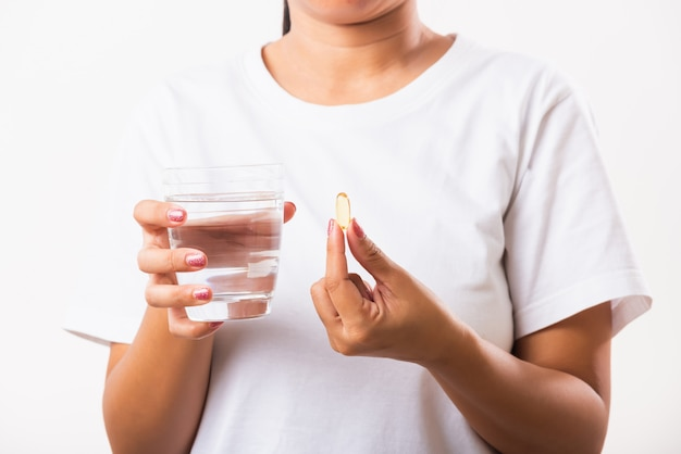 女性は準備ができて魚油ビタミン剤を手に持って水を飲んで薬を飲む