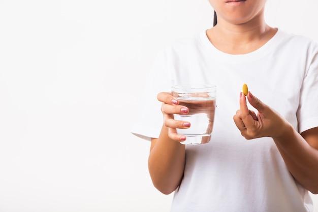女性はコップ一杯の水で魚油ビタミン剤を手に保持