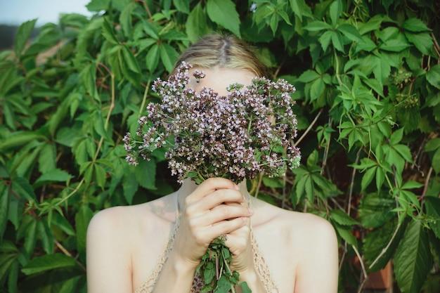 女性は新鮮なカッティングオレガノ植物の花束を保持し、緑の葉の背景、水平ライフスタイル夏の花と植物のストックフォト画像に顔を隠す