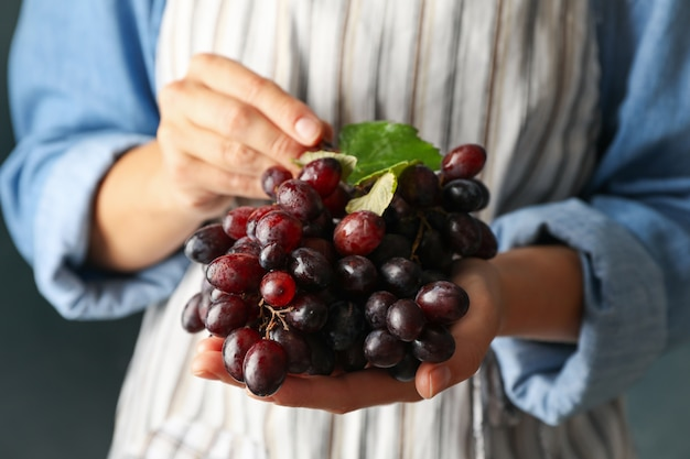 Woman hold fresh ripe grape, front view