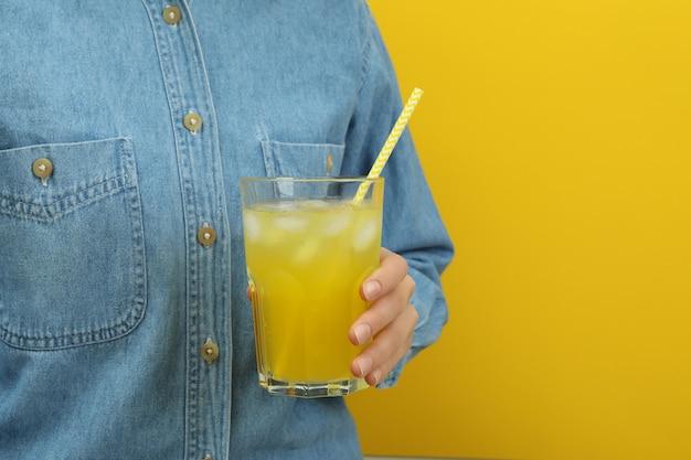 女性は黄色い表面に炭酸飲料のガラスを保持します