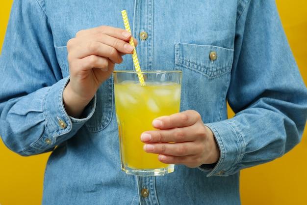 女性は黄色の壁に炭酸飲料のガラスを保持します