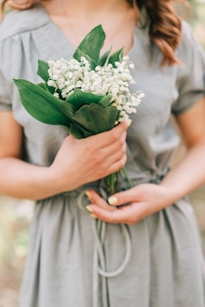 Woman hold in hand beautiful bouquet of lilies of the valley.