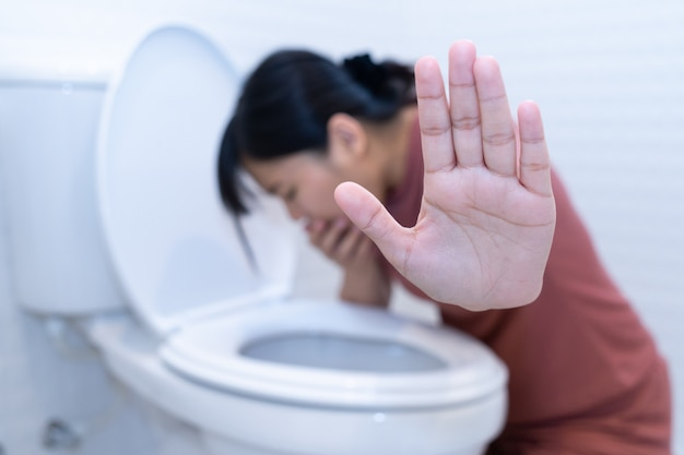 Woman hold hand and vomiting in toilet