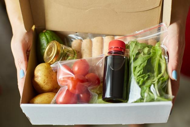 Женщина держит в руке набор еды коробки еды из свежих ингредиентов заказа от компании комплект еды, доставляется, готовит дома.